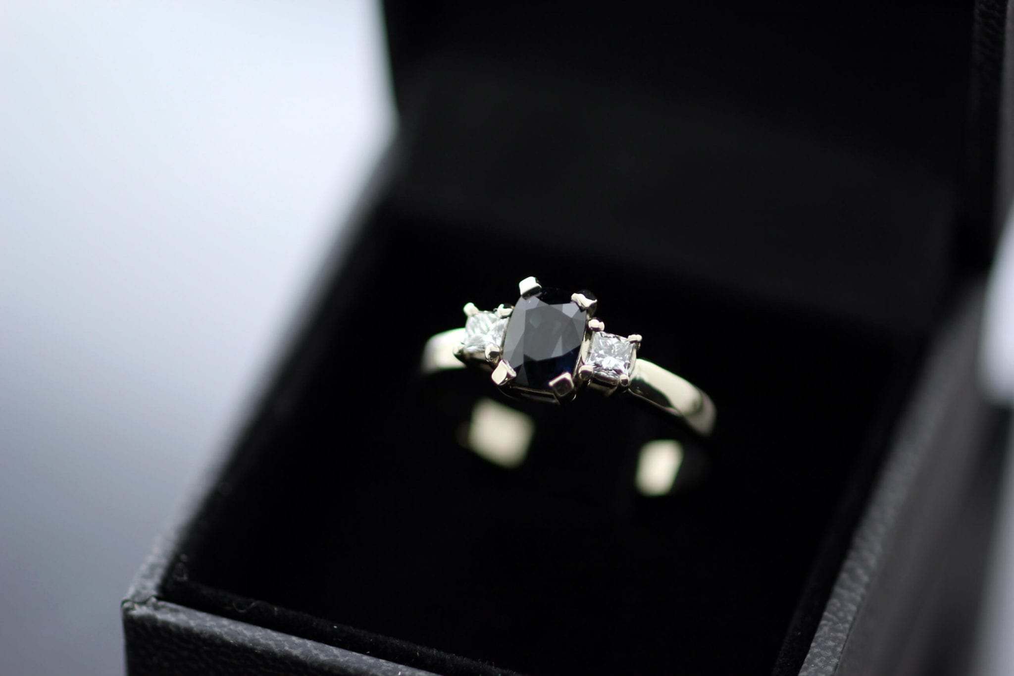 Bespoke Trilogy ring with cushion cut Sapphire, Princess cut Diamonds in White Gold