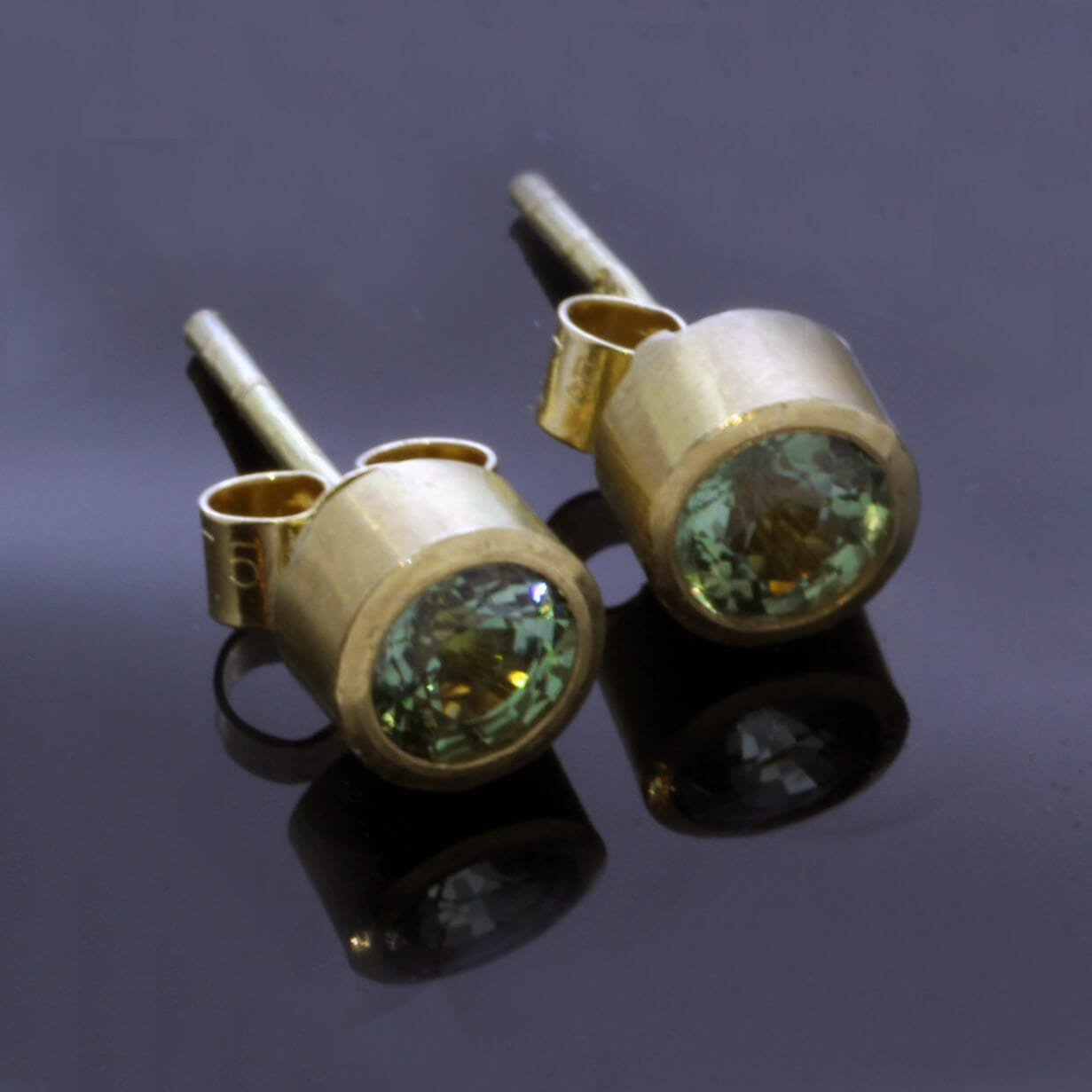 Round brilliant green sapphire gemstones set in handmade yellow gold stud earrings