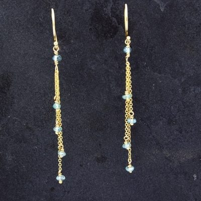 gold chain earrings on slate