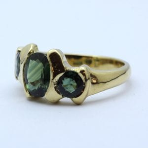 Modern Green Sapphire and Yellow Gold Trilogy ring
